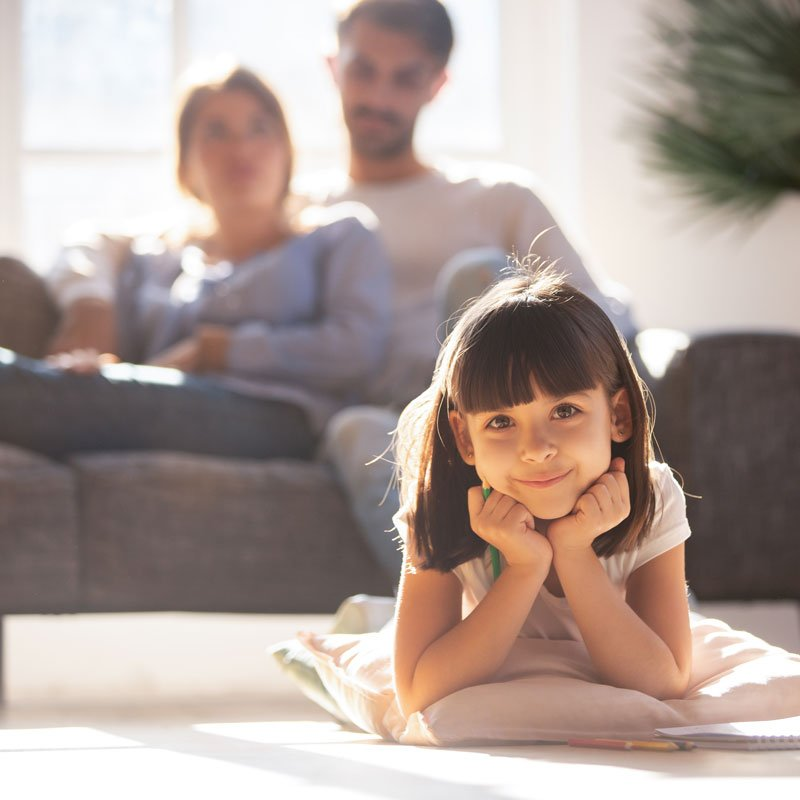 Girl laying on warm hardwood floor with parents